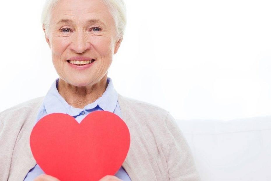 photo de grand-mère tenant un coeur rouge dans la main